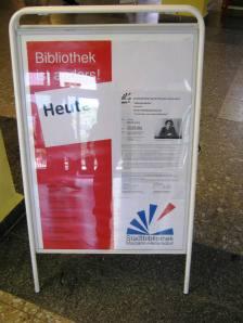 Informatiebord bij de hoofdingang van zwembad en bibliotheek